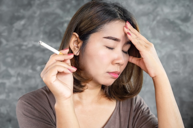 Stressed asian woman smoking cigarette over thinking Premium Photo