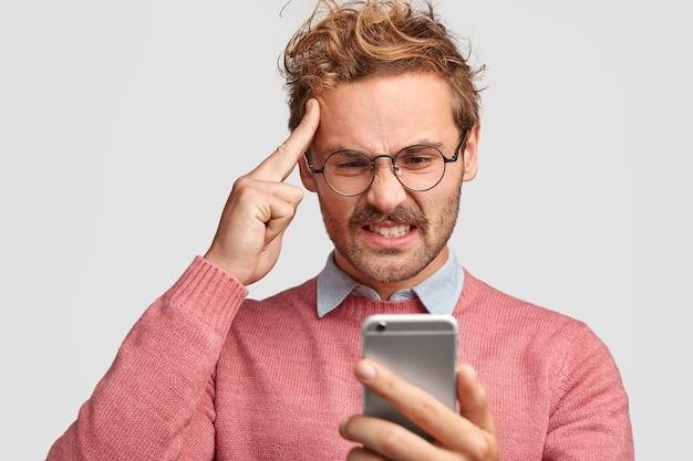 Подчеркнутый бородатый мужчина держит указательный палец на виске, недовольно смотрит в смартфон, недовольно хмурится Бесплатные Фотографии