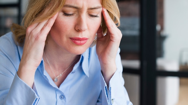 Stressed blond business woman holding head Free Photo
