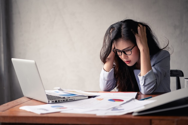 Stressed business asian woman using laptop and working Premium Photo