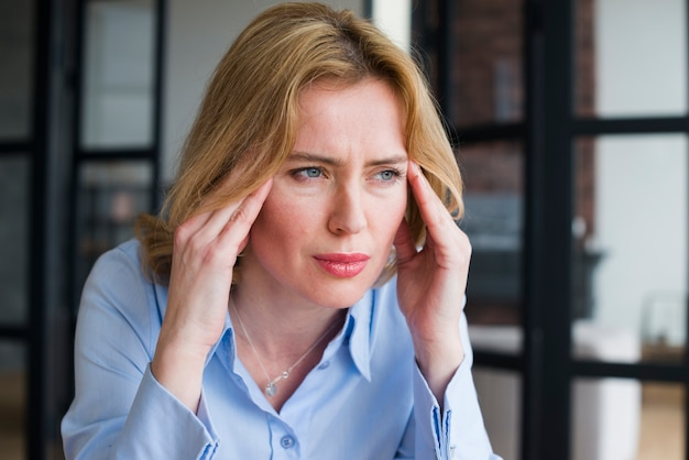 Stressed business woman holding head Free Photo