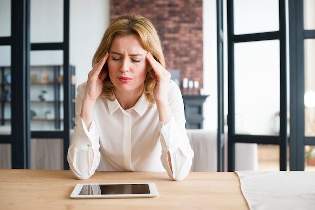 Stressed business woman sitting at table with tablet Free Photo
