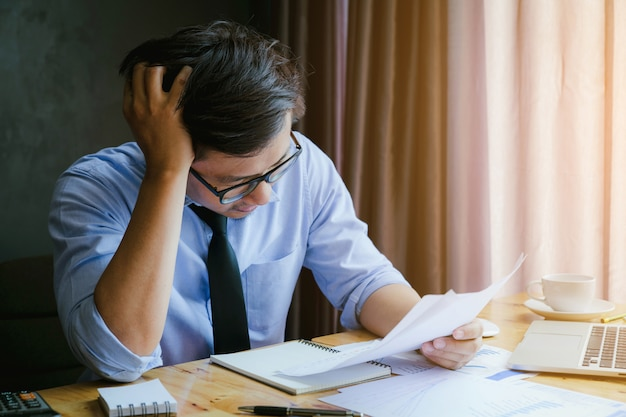 Stressed businessman.a young man sits at his desk and holds his hands on his head because of stress and summary report. Premium Photo