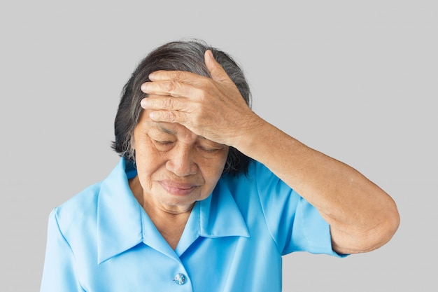 Stressed exhausted grandmother having strong tension headache on a gray background Premium Photo