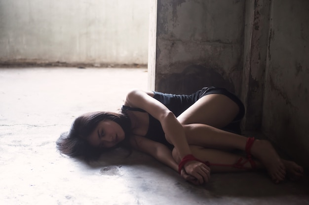 Stressed hostage tied by red rope at abandon room Premium Photo