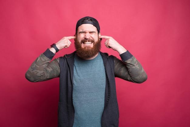 Подчеркнул человек с закрытыми глазами закрывает уши на розовом фоне. Premium Фотографии