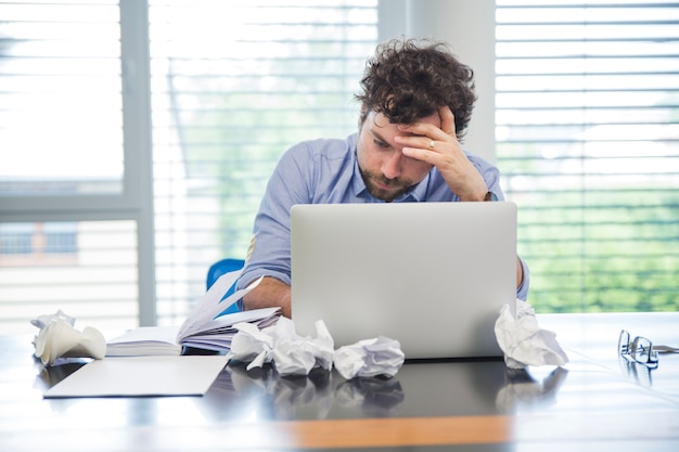 Stressed man with laptop in office Free Photo