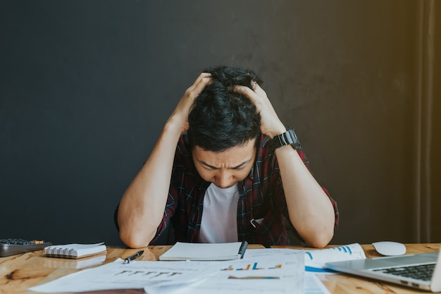 Stressed man.a young man sits at his desk and holds his hands Premium Photo
