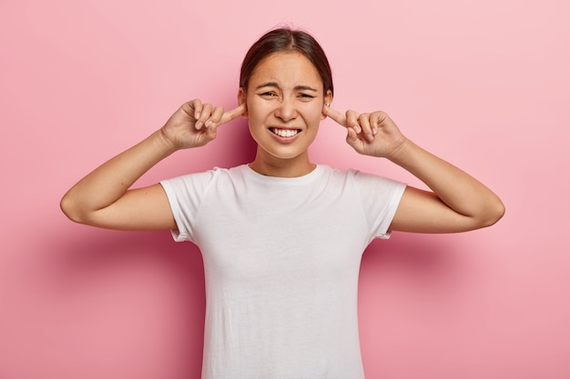 Free Photo | Stressed out asian woman annoyed with loud noise, plugs ears  with index fingers, avoids bad sound, frowns in dissatisfaction, has dark  hair, wears white t shirt, models against pink