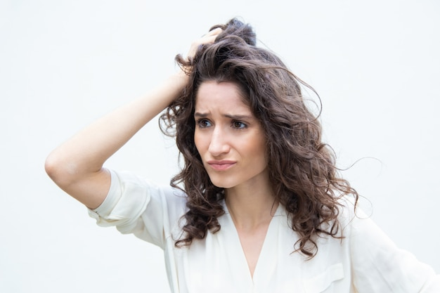 Stressed pensive desperate woman scratching head Free Photo
