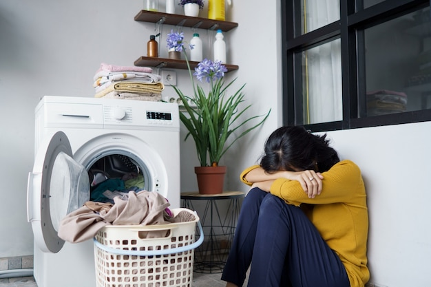 Stressed pretty asian housewife doing some laundry at home Premium Photo