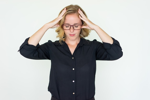 Stressed pretty young woman touching head Free Photo