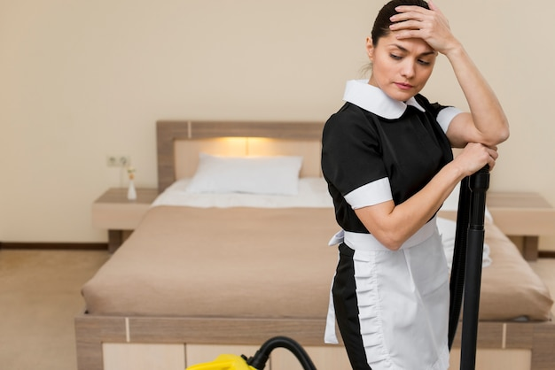 Stressed or sad chambermaid in hotel room Free Photo
