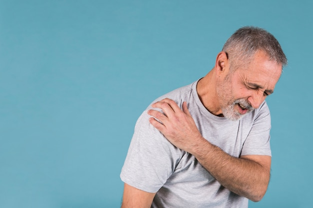 Stressed senior man with shoulder pain on blue backdrop Free Photo