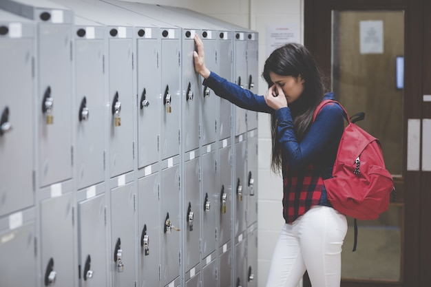 Stressed student beside her locker at the university Premium Photo