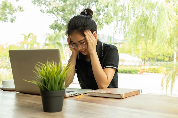 Stressed student feeling sudden pain after long using laptop for study. Premium Photo