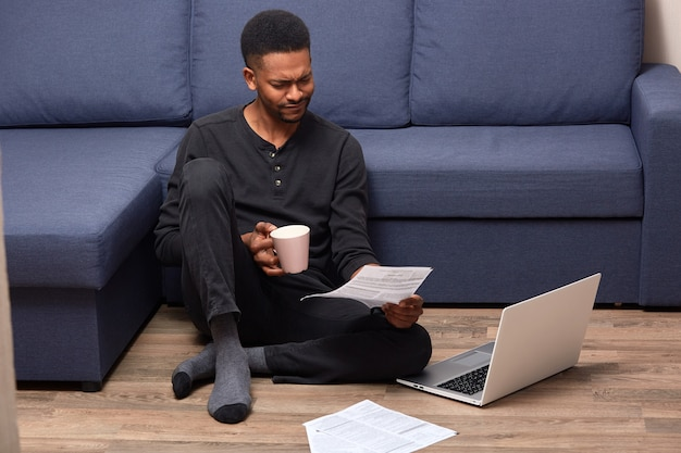 Stressed upset man sitting on floor holding rose cup with drink and document in both hands, reading attentively, using his laptop Premium Photo