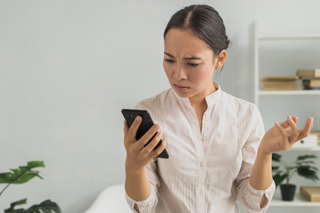 Stressed woman at office checking phone Free Photo