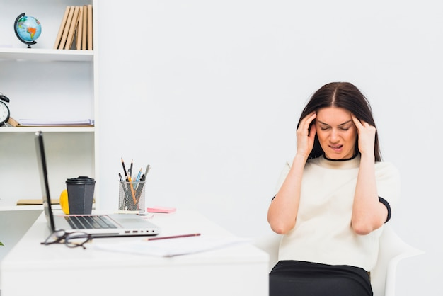 Stressed woman sitting at table in office Free Photo
