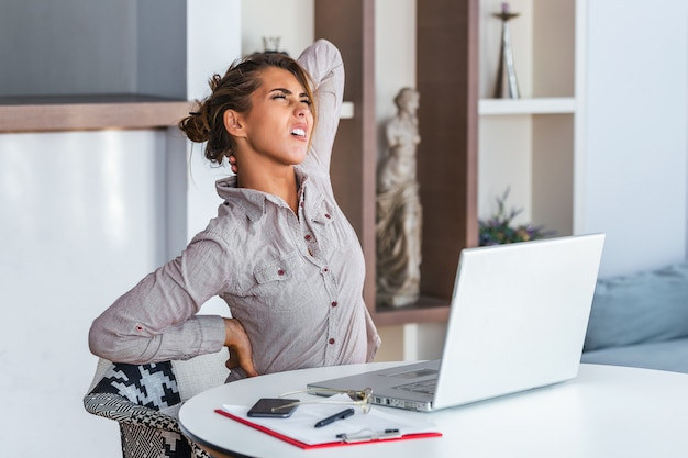 Stressed woman suffering from back pain after working on pc Premium Photo