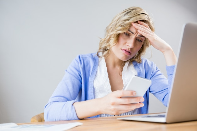 Stressed woman using mobile phone Free Photo