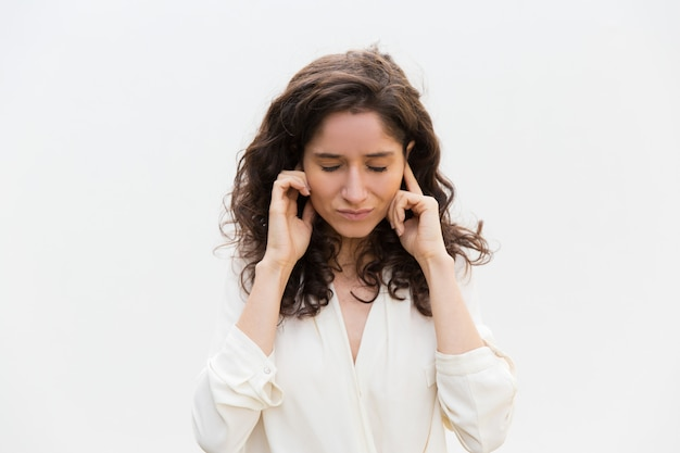 Stressed woman with closed eyes plugging ears with fingers Free Photo