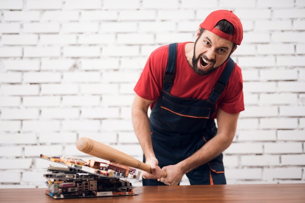 Stressed worker ruins pc boards with baseball bat. Premium Photo