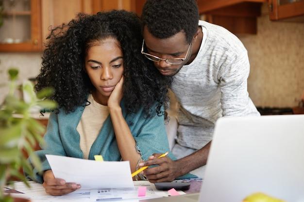 Sottolineato giovane coppia afro-americana che lavora insieme tramite documenti Foto Gratuite