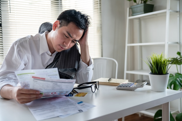 Stressed young asian businessman holding so many expenses bills such as electricity bill,water bill,internet bill,cell phone bill and credit card bill in his hand no money to pay debt Premium Photo