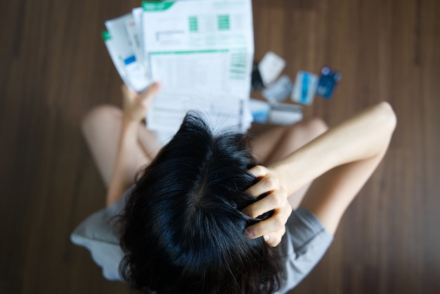 Stressed young asian woman holding bills and thinking about  finding money to pay bill. Premium Photo