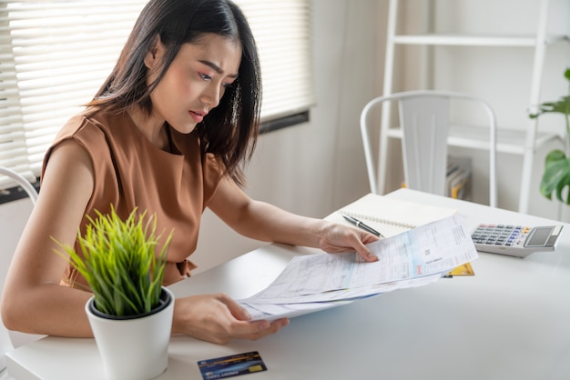 Stressed young asian woman no money to pay debt looking monthly expenses bills on table Premium Photo