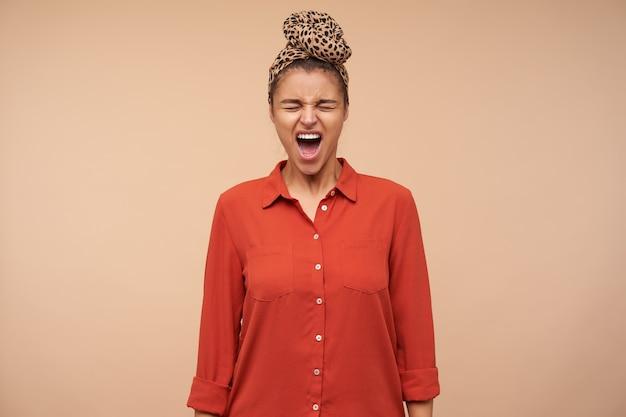 Sottolineato giovane donna bruna dai capelli castani con fascia aggrottando le sopracciglia il viso mentre urla con gli occhi chiusi, in posa sopra il muro beige con le mani verso il basso Foto Gratuite