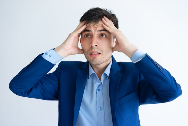 Stressed young business man touching head Free Photo
