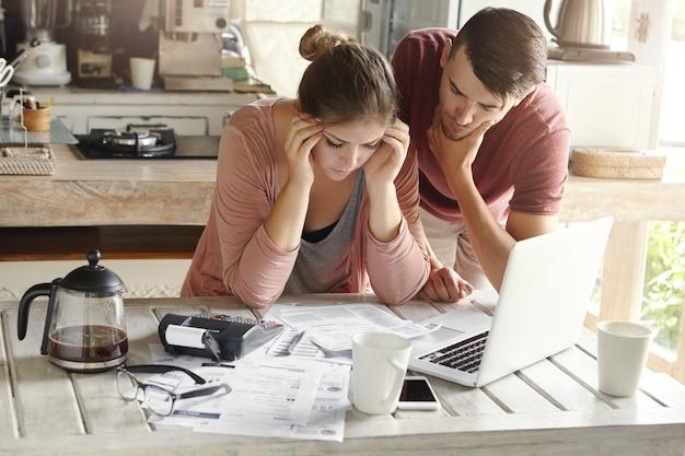 Giovani coppie caucasiche sollecitate che affrontano i problemi finanziari Foto Gratuite