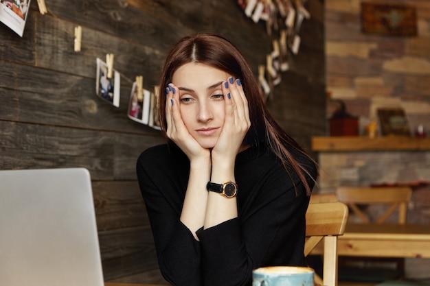 Freelancer femminile caucasico giovane sollecitato che riposa fronte sulle sue mani che esaminano lo schermo del computer portatile davanti lei con l'espressione annoiata, sentendosi stanco mentre lavorando a distanza al caffè. persone e stile di vita Foto Gratuite