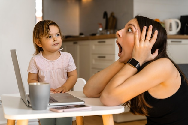 Stressed young woman working from home with small child. home office of single mother Premium Photo