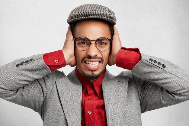 Stressante uomo barbuto con berretto e giacca, copre le orecchie, si protegge dal rumore, Foto Gratuite