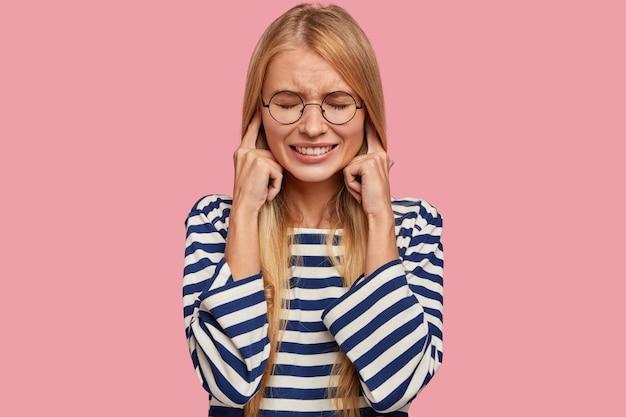 La donna bionda stressante tappi le orecchie, fa una faccia ironica, ignora i suoni sgradevoli Foto Gratuite