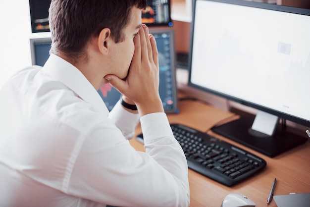 Stressful day at the office. young businessman holding hands on his face while sitting at the desk in creative office. stock exchange trading forex finance graphic concept Free Photo