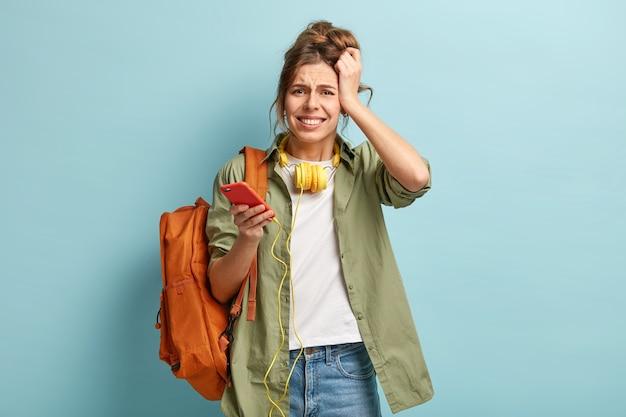 ストレスの多い不満のヒップスターの女の子は、大音量の音楽のヘッドフォンを長時間聞いた後、頭痛がした、現代の携帯電話を保持しています 無料写真