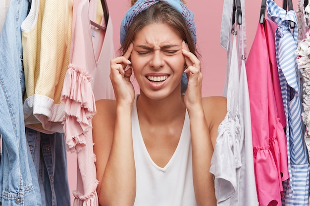 Stressful female going to cry while standing near variety of clothes, having problems while deciding what to wear Free Photo
