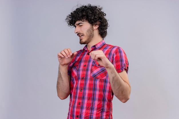 Un bell'uomo stressante con i capelli ricci in camicia a quadri che spinge via con le mani Foto Gratuite