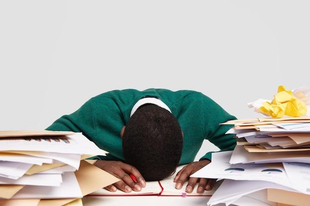 ストレスの多い仕事中毒は、机の上に頭を下げ、疲れや過労を感じ、多くの仕事をし、次の試験の準備をし、日記に情報を書きます 無料写真