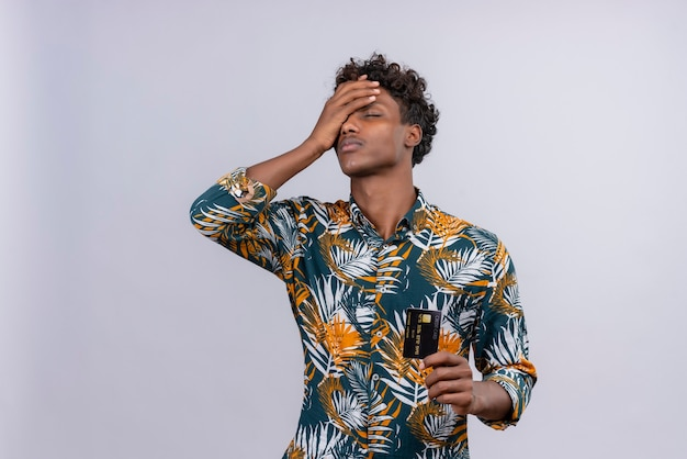 白い背景の上の手のひらで額に触れて目を閉じたまま葉を印刷したシャツにクレジットカードを示す葉の巻き毛を持つストレスの多い若いハンサムな浅黒い肌の男 無料写真