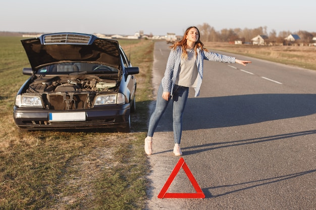 Stressful young woman driver hitchhikes and stops cars, asks for help as have problem with brocken car Premium Photo