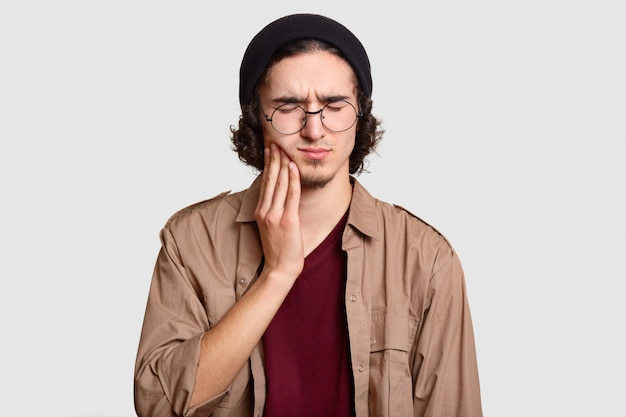 Stressful youngster with small beard keeps hand on cheek, suffers from toothache, keeps eyes shut, dressed in stylish clothes, big round spectacles, models on white wall. Free Photo