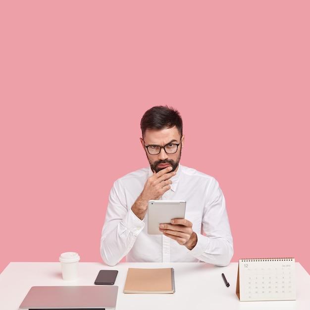 Il rigoroso responsabile amministrativo controlla la posta elettronica sul touchpad, si gode la sua occupazione, vestito con abiti formali Foto Gratuite