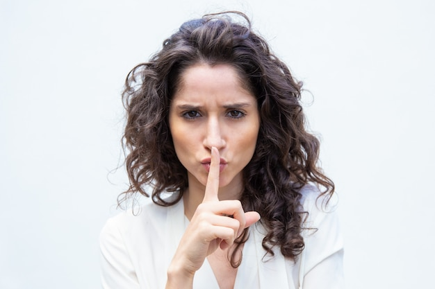 Strict beautiful woman making shh gesture Free Photo