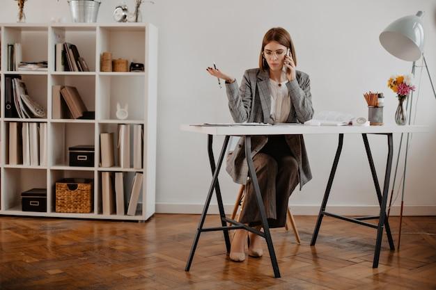 厳格なビジネスウーマンは、明るいオフィスに座って、電話でクライアントと交渉します。 無料写真