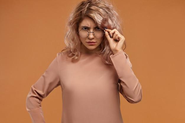 Insegnante femminile alla moda rigoroso che abbassa gli occhiali e fissa la macchina fotografica con l'espressione facciale scontenta, aspettando la risposta Foto Gratuite